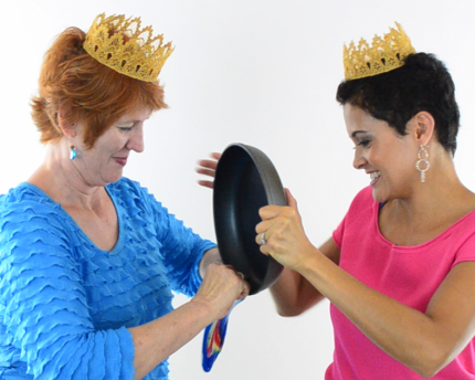 two people trying to stuff a frying pan into a balloon